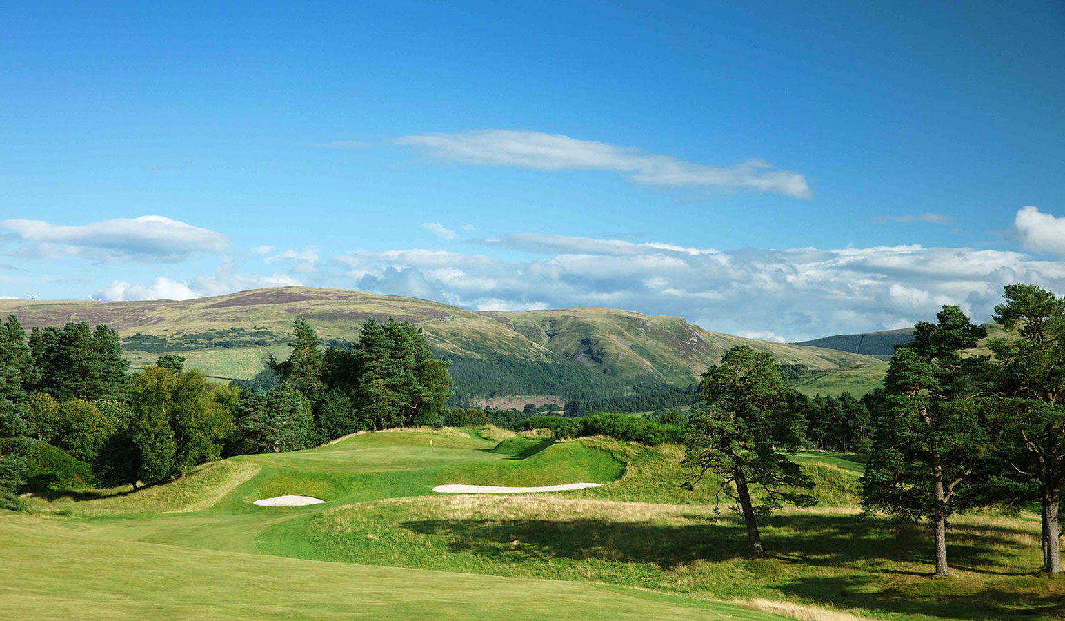 A view of the Gleneagles golf courses on a blue sky day with the Ochil Hills in the background
