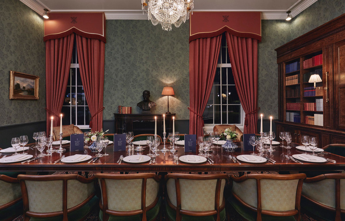 A large mahogany table laid for dinner with silver cutlery and candelabras