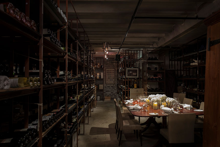 Long wine racks with hundreds of bottles of wine surround an intimate table set for 8 in the atmospheric cellars