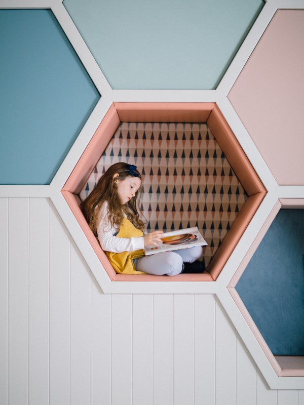 A girl reads a book in a hexagonal cubby hole seat in The Den