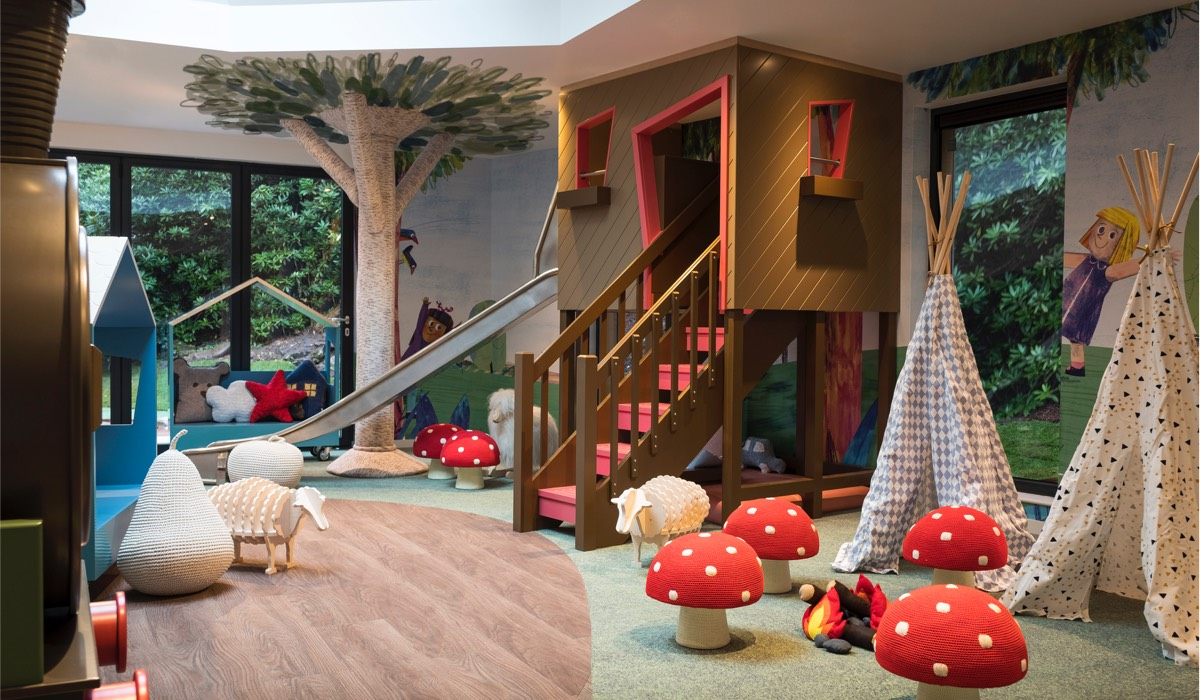 A treehouse climbing frame, teepees, mushroom shaped stools and wooden toys in Little Glen
