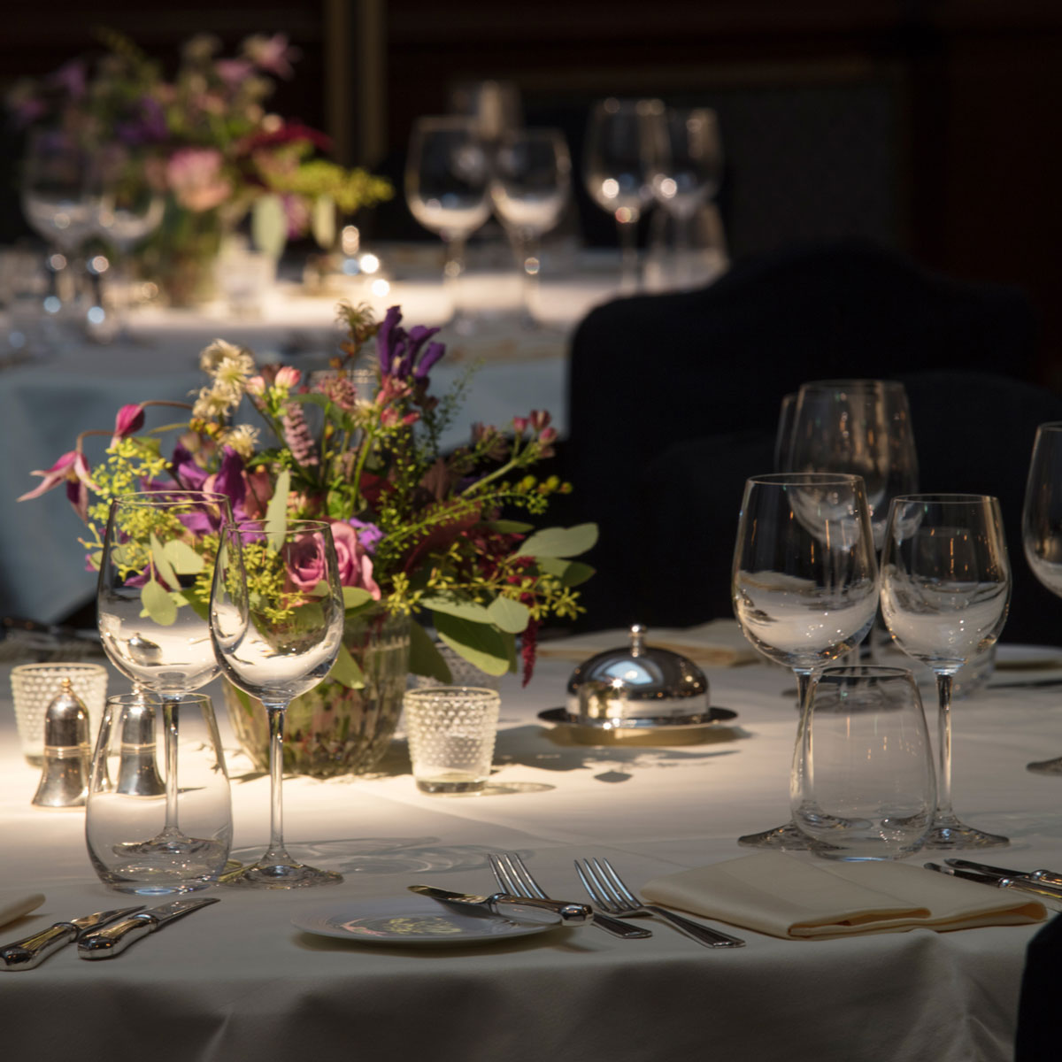 Silver service set out on dinner tables in the Henry hall
