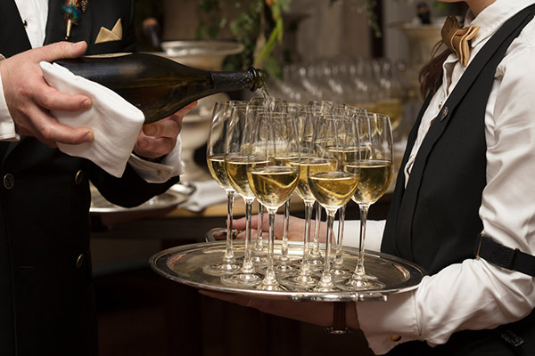 Two waiters pour a tray full of champagne flutes