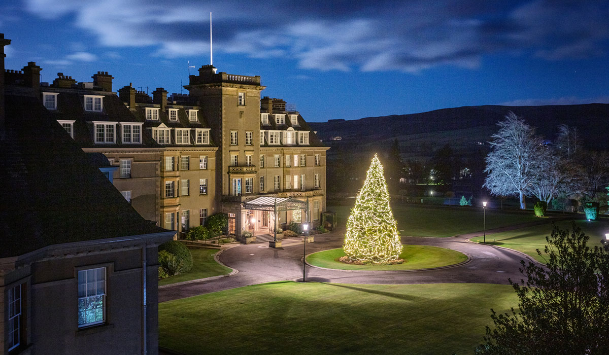 A shot of the front of the Gleneagles hotel at night with brightly lit Christmas tree